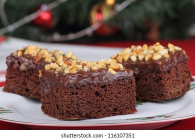 Closeup of chocolate brownies on a plate with Christmas decorations in background