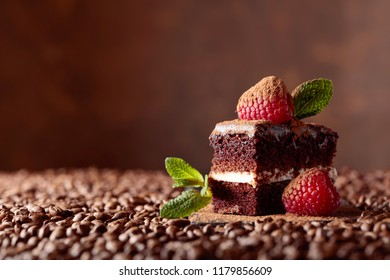 Closeup of chocolate cake with raspberry and mint on a brown bacground. Copy space.