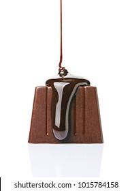 Close-up chocolate candy pouredliquid black chocolate isolated on white background