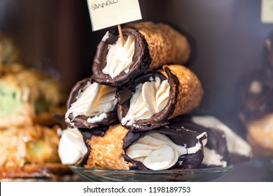 Closeup of chocolate cannoli stuffed with cream cheese whipped filling dessert on glass plate window display in gourmet bakery Italian cafe with golden crust, cannolo sign