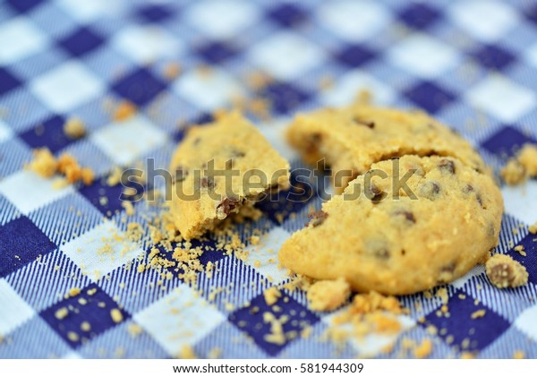Closeup of chocolate chips cookies on fabric pattern.