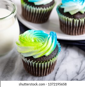 Closeup of a chocolate cupcake with buttercream icing and glass of milk and cupcakes in background