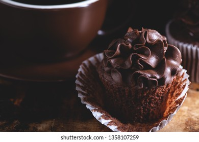 Closeup of a chocolate cupcake with a coffee cup on a dark background
