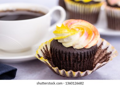 Closeup of a chocolate cupcake with colorful buttercream icing and cupcakes and cup in background