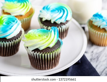 Closeup of a chocolate cupcakes with buttercream icing on a plate and glass of milk in background