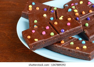 closeup chocolate fudge brownies with candy pieces on blue plate