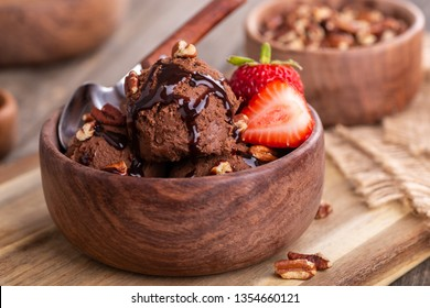 Closeup of a chocolate ice cream sundae with fresh strawberries in a wooden bowl