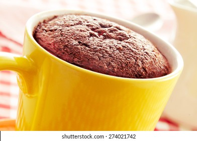 closeup of a chocolate mug cake in a yellow porcelain mug on a set table covered with a checkered tablecloth