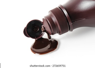 closeup chocolate syrup pouring on white background