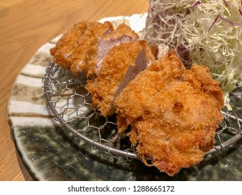 Closeup to chopped tonkatsu (pork cutlet) with shredded cabbage in background