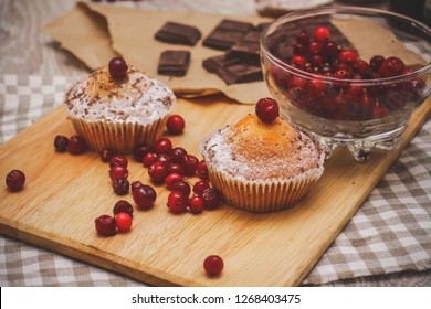 Close-up of a chopping light board on a linen linen napkin, on which red berries, muffins, chocolate Festive pastry composition.