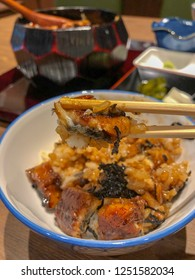 Closeup to chopsticks with a bite of eel (unagi) and rice,a bowl filled with steamed white rice,topped with fillets of eel (unagi),glazed with a sweetened soy based sauce, called tare and caramelized.