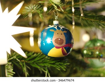 Closeup of christmas ball with a reindeer hanging on decorated christmas tree