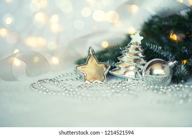 Closeup of Christmas decorations and fir branches on the snow. Blurred, sparkling background. Retro filter effect. Copy space. Selective focus.