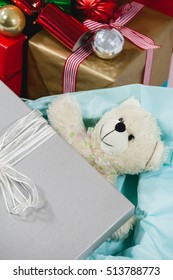Close-up of christmas presents with soft toy and decoration