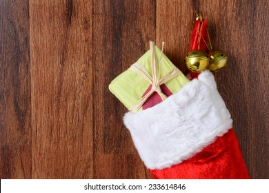 Closeup of a Christmas stocking filled with presents hanging from a hook on a wood wall. Two jingle bells also hang from the hook in horizontal format.