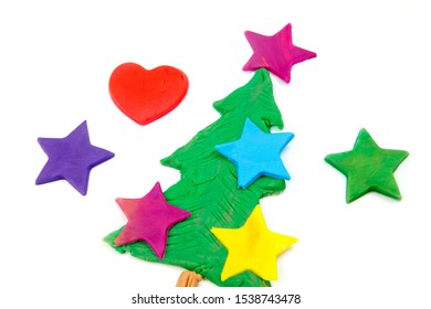 close-up of a christmas tree and colorful stars on white made out of play dough