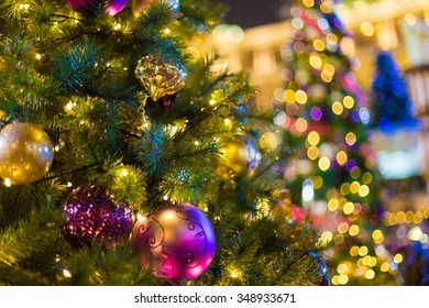 Closeup of Christmas tree at night with yellow light decorations