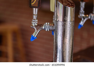 Closeup of chrome keg tapper with water sweat beads and tap handles at walk up bar at outdoor wedding reception