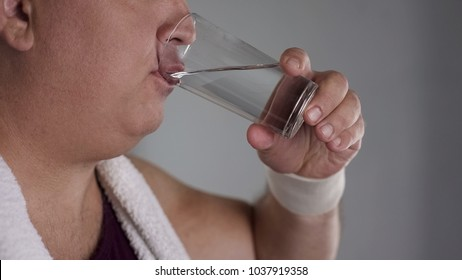 Close-up of chubby man drinking fresh water from glass, healthy weight loss diet