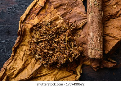 Close-up of cigar and pile of tobacco and dried tobacco leaf on wood background dark top view