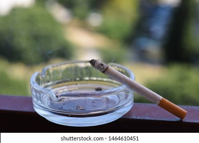 Closeup of cigarette on ashtray/ A cigarette on the edge of a typical ashtray