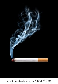 Closeup of cigarette on ashtray with wisp of smoke. Isolated