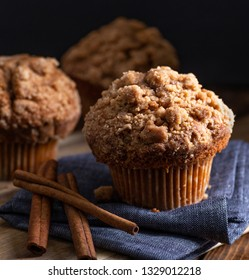 Closeup of a cinnamon muffin and sticks on a blue napkin with muffins on a dark background