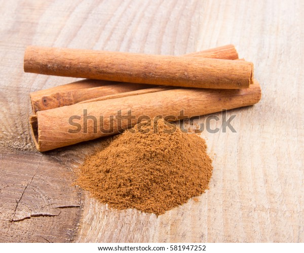 Close-up of cinnamon sticks on a wooden background.