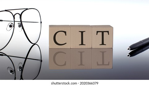 Close-up Of CIT Wooden Blocks on black background with glasses and pen