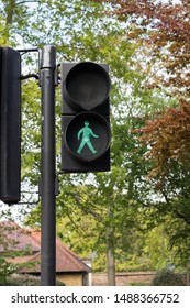 Close-up: City Traffic Light is Green for Pedestrians. You Can Cross the Street. Simple Rule for Everybody. Pay Attention to Your Way. Vertical Image.
