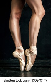 Close-up classic ballerina's legs in pointes on the black wooden floor