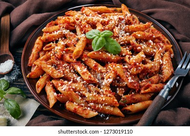 close-up of classic italian penne arrabiata on a clay plate with fresh basil and grated pecorino cheese on a rustic table with brown cloth, view from above