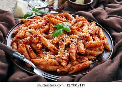 close-up of classic italian penne arrabiata with hot tomato sauce on a clay plate with fresh basil and grated goat cheese on a rustic table with brown cloth, view from above