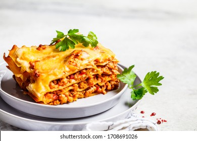 Close-up of classic meat lasagna with cheese on a gray plate. Italian food concept.