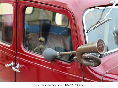 Closeup of an classic old brass hooter or a horn of vintage red car.