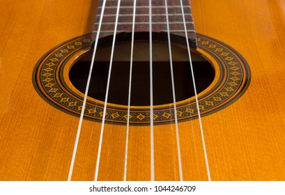 Close-up of a classical guitar's body with the sound hole in the center