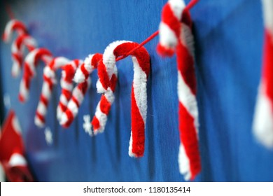 Close-up of classroom door decoration, candy canes made of pipe cleaners in red and white colors, in soft focus in the background.