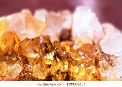 Close-up of clasters of yellow quartz crystals background. Texture of quartz crystals. Raw specimen of quartz crystal stone. Citrine yellow gem crystals geological mineral background. Selective focus