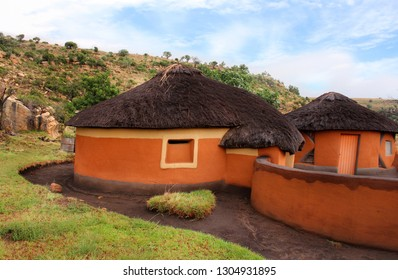 Close-up clay rondavel with straw roof. Basotho tribe village. South Africa. The round huts are the traditional African houses. Drakensberg mountains background. Ethnic tribal building.