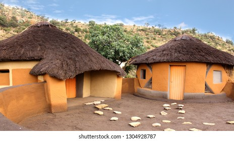 Close-up clay rondavels with straw roof. Basotho tribe village. South Africa. Traditional round huts surrounded by the wild untouched nature. The cozy courtyard.