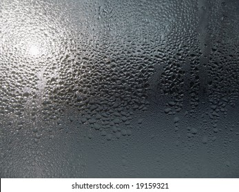 Close-up clear drops of water on window glass surface
