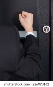 Close-up of clenched fist knocking on the door