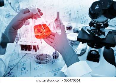 Close-up of clinician working with tools during scientific experiment in laboratory with chemical table background