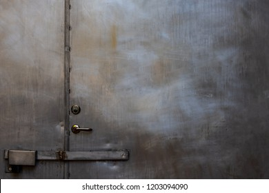Closeup of closed scratched grungy shiny steel door with locks and handle.