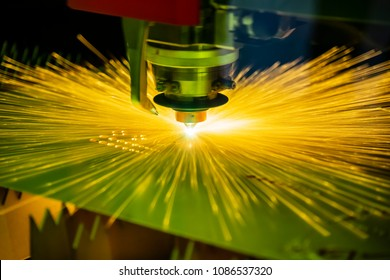 Close-up of the CNC laser cutting machine cutting the metal plate with the sparking light. Modern sheet metal manufacturing process.