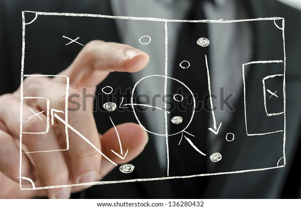 Closeup of coach pointing to a football strategy plan drawn on a virtual screen.