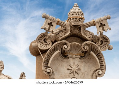 Close-up of the Coat of arms of the Vatican city with the papal Tiara, the shield and the two keys with a cross. Colonnade of the Basilica of Saint Peter, Rome, Latium, Europe