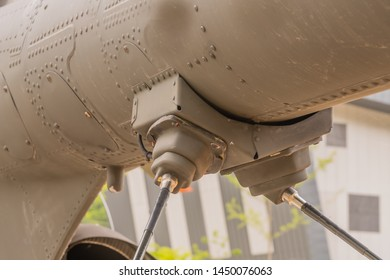 Closeup of coaxial radio antenna attached to undercarriage of army helicopter tail boom.