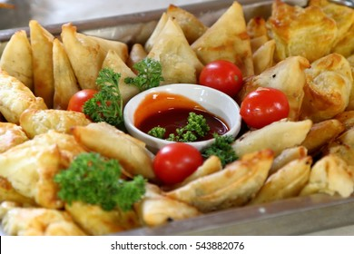 Close-up of cocktail food platter for functions (shallow depth of field). Plate includes pastries and samoosas (Indian food)